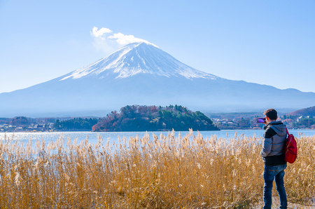 Photographer man standing outdoor photography by a mobile amidst the beautiful nature of Mt. Fuji at Yamanashi in Japan with lake kawaguchiko. Travel and Attractions Concept. Stock Photo