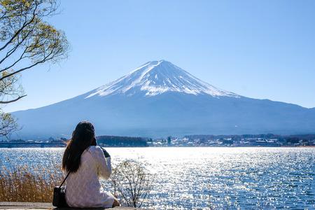 Woman sitting on a ground at kawaguchiko lake, Japan. View of fuji mountains.