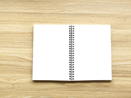 Top view of blank open notebook page on the wood background office desk with little tree. Minimal flat lay style