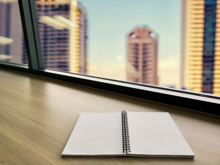 open white notebook on wood table in modern room with the big windows in office buildings city background.