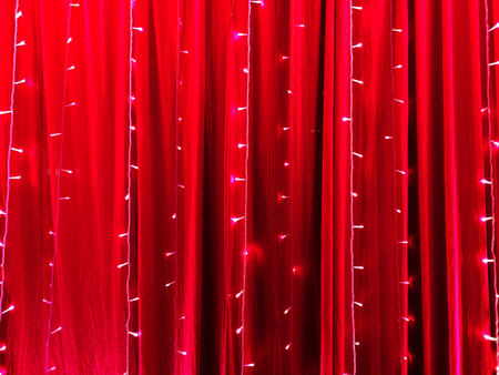 LED-Leuchten auf rotem bestimmtem Stoffhintergrund als abstrakter Hintergrund.