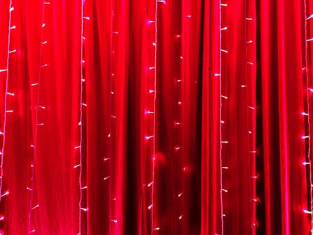 Luci a LED su uno sfondo di tessuto rosso come sfondo astratto.