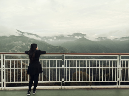 Asian woman standing alone on balcony looking at white foggy and mountains background