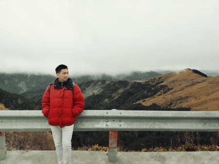 Young Asian Man Enjoying in the Wind and Mist on Mountain Top with Beautiful Landscape in Background.