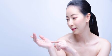 Beauty Spa Asian Woman with perfect skin Portrait. Beautiful Japanese Spa Girl showing empty copy space on the open hand palm for text. Proposing a product. Gestures for advertisement. Blue background