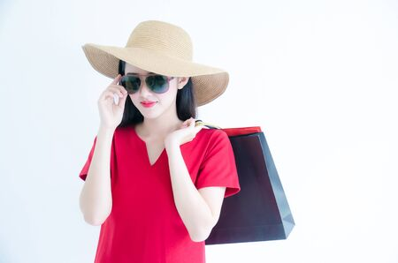 Young beautiful fashionable Asian woman holding shopping bags wearing red dress, sunglasses and hat over white background studio shot