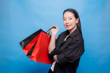 Portrait of a happy Chinese woman in black shirt holding shopping bags isolated on a blue background Stock fotó