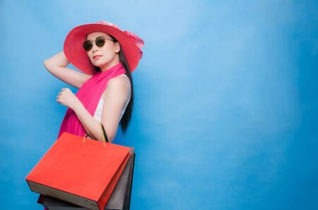 Portrait of an excited beautiful girl wearing dress (white T-Shirt), pink hat and sunglasses holding shopping bags isolated over blue background