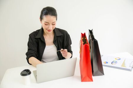 Young woman holding credit card and using laptop computer. Online shopping concept Stock fotó