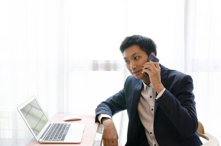 Young Asian Businessman speaking on the phone, looking at computer and thinking to make decision for a deal Stock fotó