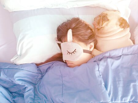 Sweet asian woman with mask and cute puppy pug dog is sleeping rest in a bed. Stock fotó