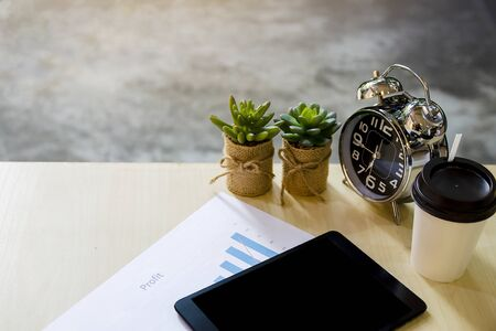 Modern workplace with digital tablet, nature cactus tree, mobile phone, clock, cup of coffee and papers with profit numbers Stock fotó