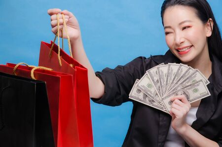 Portrait of a happy Chinese woman in black shirt holding red shopping bag and money isolated on a blue background