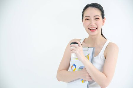 Pretty young asian business woman holding a cup of coffee and document files. Isolated Studio portrait on white background Stock fotó