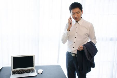 Bad news, Serious Asian businessman standing in office, talking by mobile phone and looking away on white background with desktop and laptop Stock fotó