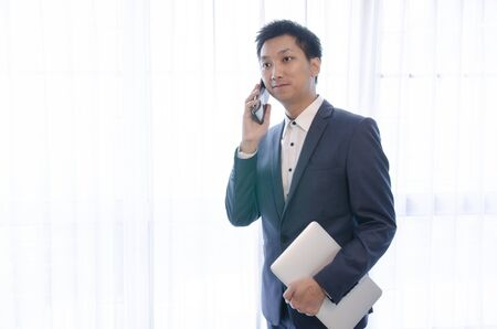 Young handsome asian business man in blue jacket suit, business style, white shirt, isolated, white background, smiling, standing and looking confident, holding laptop, talking on smartphone