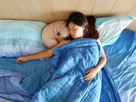 Beautiful young woman or girl cuddles and hugs her best friend pug puppy dog, sleep together under blankets in hipster designer bed on cold day, peace and quiet