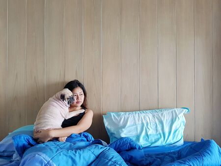 Beautiful young woman or girl cuddles and hugs her best friend pug puppy dog, sleep rest together under blankets in hipster designer bed on cold day, looks and thinking forward