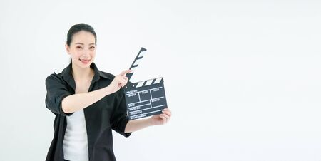 An attractive young asian woman holds an open film slate on white background Standard-Bild - 129624674