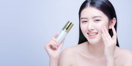Beauty treatment. Asian woman applying moisturizing cream on face, holding bottle with skin care product, studio shot on blue background Stock Photo