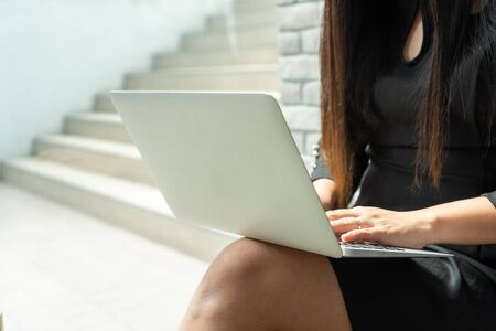 Close-up view of modern businesswoman typing on keyboard. Hold white laptop on legs. Busy by working on remote project. Alone in room or coffee cafe shop. Modern housewife in black dress. Stock fotó