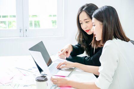 Twee jonge Aziatische vrouwen in kantoor werken en gelukkig samen op desktop.