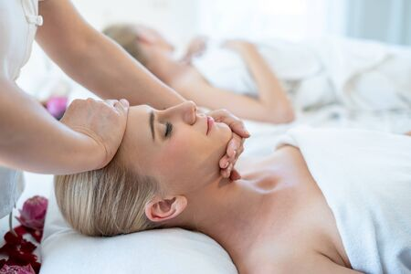 Foreign women are happy and relaxed with a Thai massage on the head by a professional Thai masseuse while lying on the bed. Facial massage is one of the world famous relaxation.