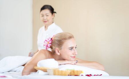 Foreign woman are happy and relaxed with Thai massage by a professional Thai masseuse. Oil massage is one of the world famous relaxation. (call Nuad Thai, traditional Thai massage )