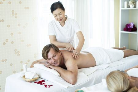 Foreign men are happy and relaxed with Thai massage by a professional Thai masseuse while the wife is sleeping on the face mask beside. Oil massage is one of the world famous relaxation.