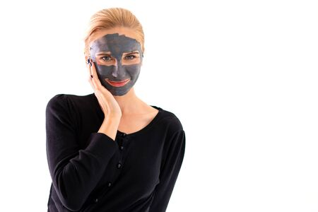 Smiling woman on casual dress with purifying black mask on her face isolated on white background Reklamní fotografie