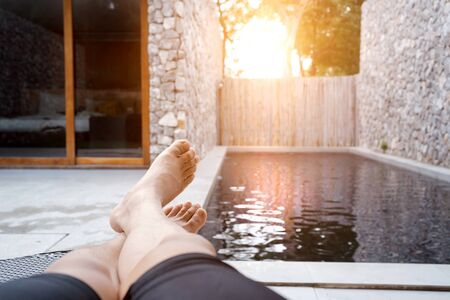 Man feet on sun bathing bed resting relaxing beside private swimming pool. leisure vacation lifestyle. Summer concept about people lying on deck chair in vacation