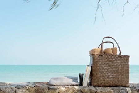 Weaving bag or Basket with towel, bottle of sun screen or sunscreen lotion, swimming robe and book next to a sea beach, summer travel concept for a rest in vacation time with copy space Reklamní fotografie