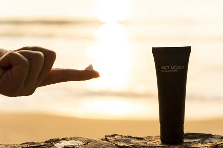 The silhouette of a young woman's hand with a lotion on the finger and a body lotion bottle packaging on the beach in the morning with the light of the sunrise in the background. For Advertisement Reklamní fotografie