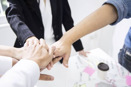Colleagues are gathering hands to encourage each other to work. For successfully complete project. Employees are working in modern office. (Agile and Scrum in retrospective and sprint review process)