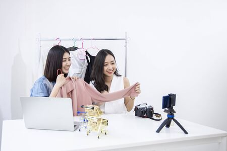 Beauty asian Vlogger blogger selling woman clothes and bag online during using phone online on social media. Women coaching trading and review product. Business presentation. Selfie in smartphone