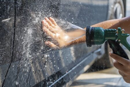 Woman hand was washing the car with water jet spray and using her bare hands to rub dirt and dust from the car to prevent scratches from the car