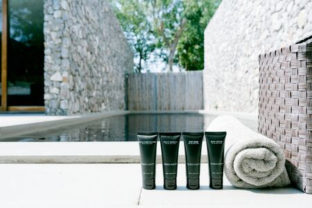 (Blank Label) Mini plastic tube with cosmetic products and towels and basket beside swimming pool against sun light. Hotel amenities such as hair shampoo, hair conditioner, body wash and body lotion