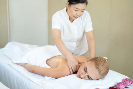 Beautiful caucasian woman sleeping rest relax on bed for spa asia massage at luxury spa and relaxation. Thai masseuse massaged her back and shoulder in the spa room for office syndrome treatment