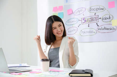 Smiling beautiful asian woman celebrate with laptop happy for success working. Agile for startup small business concept at modern office or co-working space with copy space for label text
