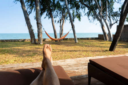 Young man sleep rest relaxing under tree shade on beach on sunny summer day with hammock and sea in front of view. Vacation holidays. Man feet closeup on sunbed enjoying sun on weekend