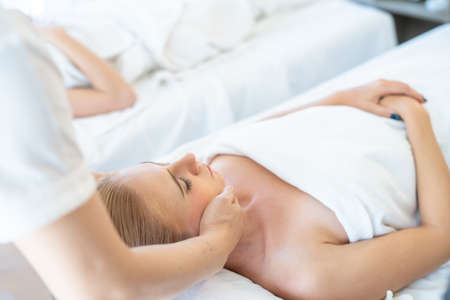 Beautiful woman lying on the bed for a spa asia massage at luxury spa and relaxation. The masseuse massaged her face and head in the spa room