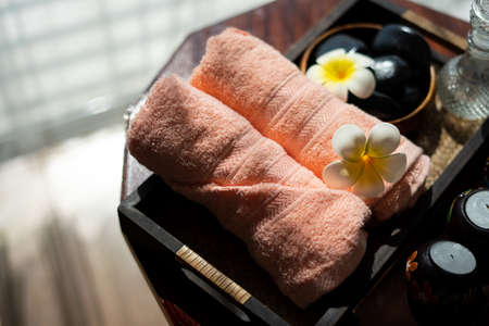 Spa accessories wellness setting with pink pastel towel, cosmetic bottles, aroma oil, white plumeria flower in tray, massage stones in wooden bowl and spa candle, spa concept, copy space Фото со стока
