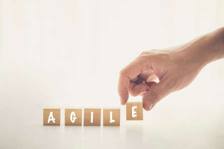 Agile and Scrum in Software Development concepts, Hand pick wooden cube and place with text to fill the word AGILE. Brochure design template, card, banner with copy space for label text 免版税图像