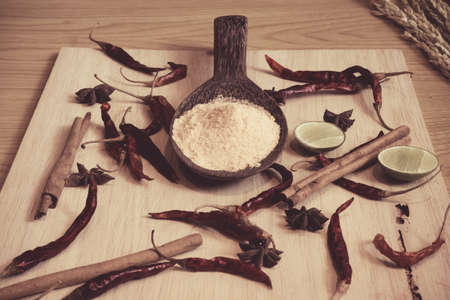 Seasoning powder in the wooden spoon decorated with lime, cinnamon, chilly on the wood plate on the table Imagens