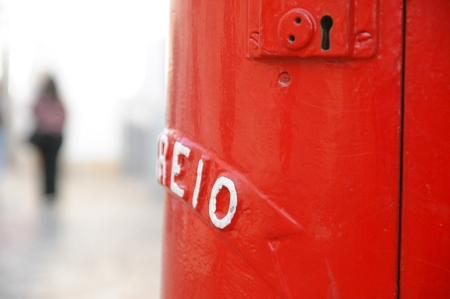 Red antique postbox and a blurred woman in background