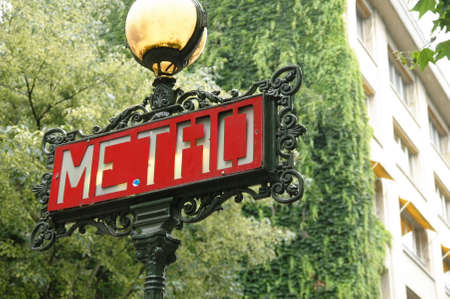 Metro sign in a lamp pole in a street of Paris, over a green background