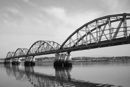Black and white railway bridge with stone columns crossing a river Reklamní fotografie