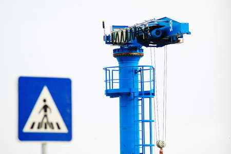 A blue heavy lift crane near a crosswalk sign at a port