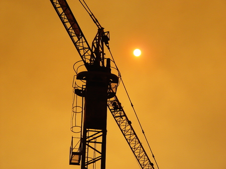 Crane silhouette over an oranje sky and a timid sun. This photo was taken during a fire. Reklamní fotografie