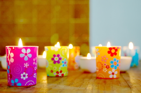 Colored glass with flowers and burning candles
